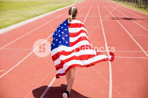 Rear view of female athlete running on the running track with american flag