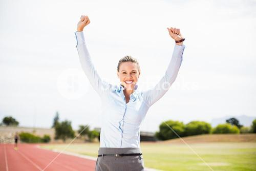 Excited businesswoman standing on the running track
