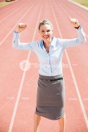 Portrait of excited businesswoman standing on the running track