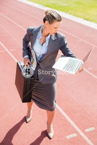 Businesswoman ready to run with a laptop and briefcase