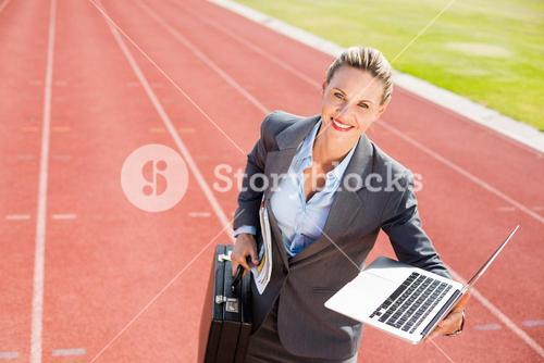 Portrait of happy businesswoman ready to run with a laptop and briefcase
