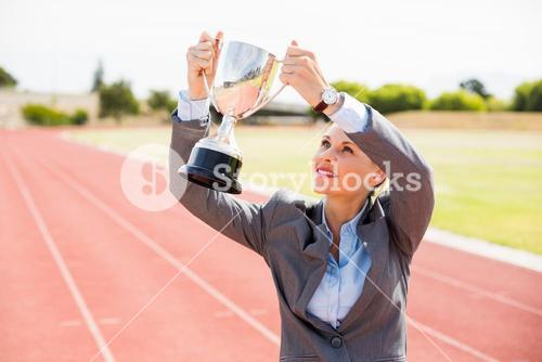 Happy businesswoman holding up a trophy