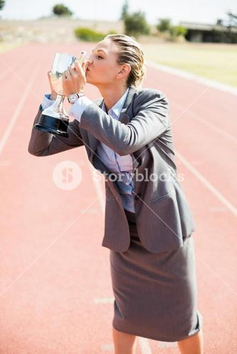 Happy businesswoman kissing her trophy