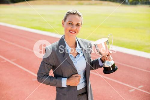 Portrait of happy businesswoman holding a trophy