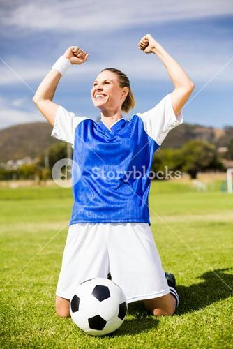 Excited football player kneeling in stadium