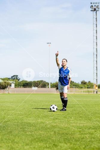 Female football player gesturing while playing football