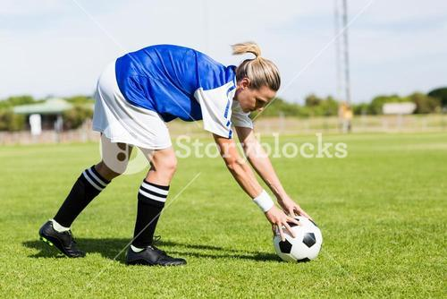 Female football player keeping a ball