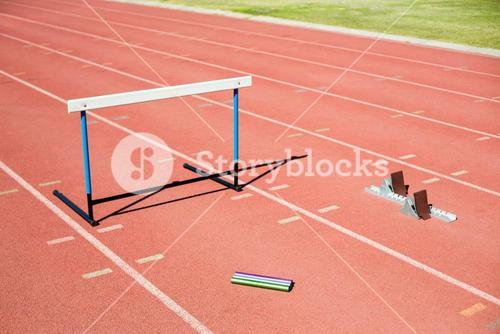 Hurdle, relay baton and a starting block kept on a running track