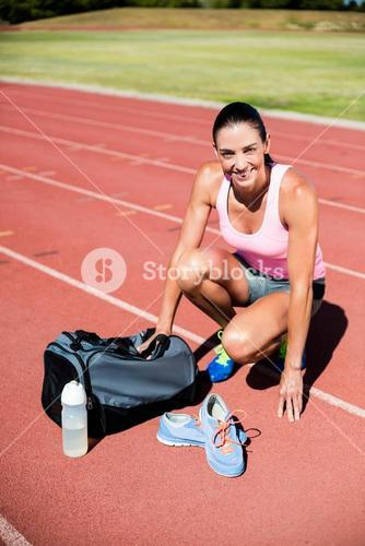 Portrait of happy female athlete with her sports accessories