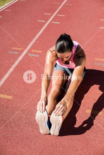 Female athlete stretching her hamstring