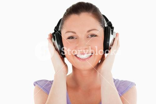 Portrait of a good looking woman posing with headphones while standing