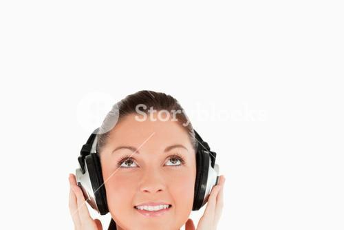 Portrait of a gorgeous woman posing with headphones while standing