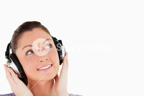Portrait of a lovely woman posing with headphones while standing
