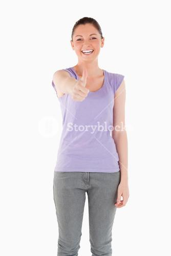 Good looking woman posing with her thumb up while standing