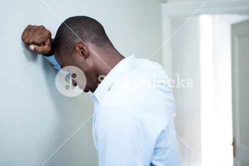 Tensed man leaning on wall