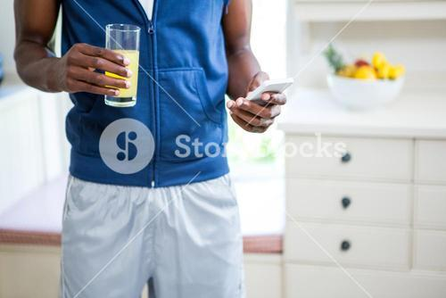 Mid- section of man holding a glass of juice while text messaging on phone