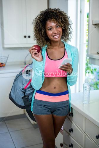 Woman with gym bag holding a apple and phone
