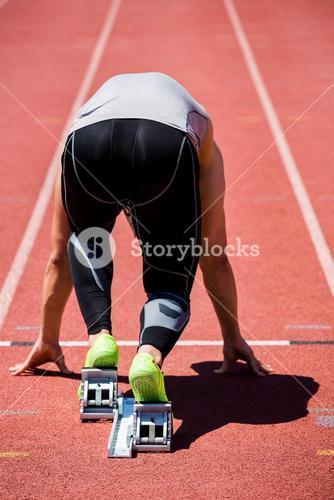 Athlete on a starting block about to run