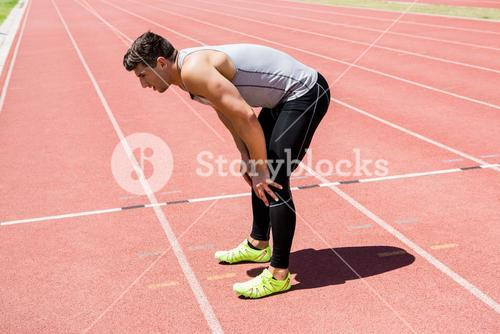 Tired athlete standing on running track