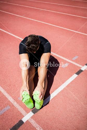 Tired athlete sitting on the running track