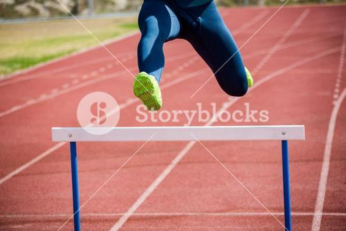 Athlete jumping above the hurdle