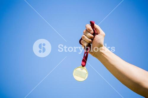 Athlete hand holding gold medal after victory