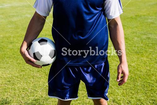 Soccer player standing with a ball