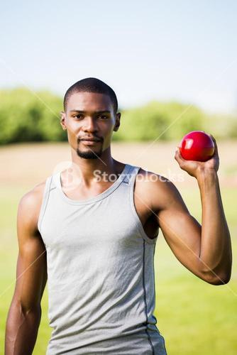 Male athlete holding shot put ball