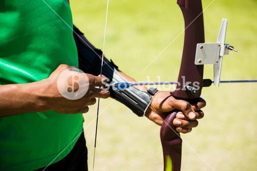 Mid section of athlete practicing archery