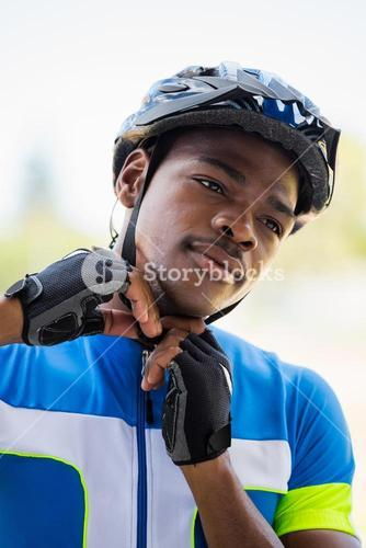 Athlete putting on cycling helmet