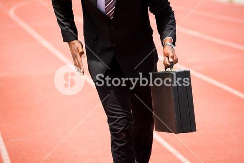 Mid section of businessman running on a running track