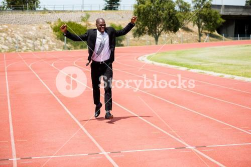 Excited businessman standing on the running track