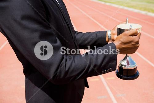 Mid section of businessman holding winning trophy