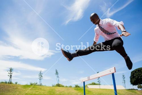 Businessman jumping a hurdle while running