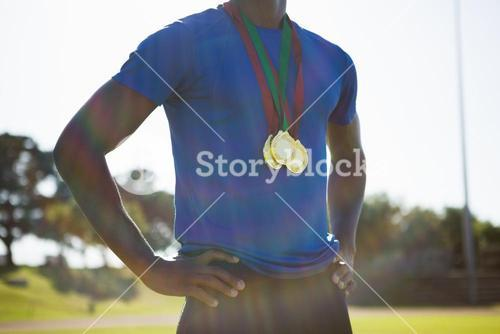 Mid section of athlete posing with gold medal after victory
