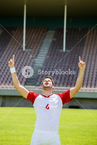 Excited football player with hands raised