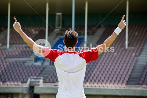 Excited football player standing in stadium