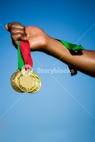 Athlete hand showing his gold medals