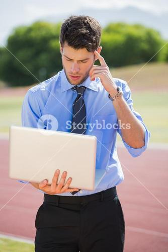 Businessman using a laptop on the running track