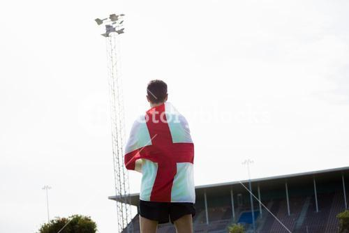 Athlete with england flag wrapped around his body