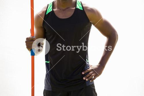 Happy athlete standing with javelin