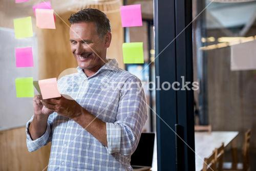 Man using mobile phone and sticky notes on window