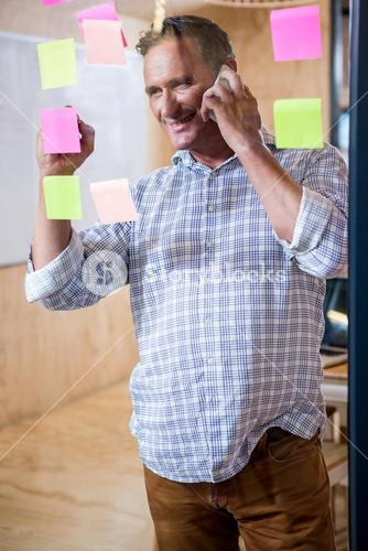 Man writing on sticky notes while talking on phone