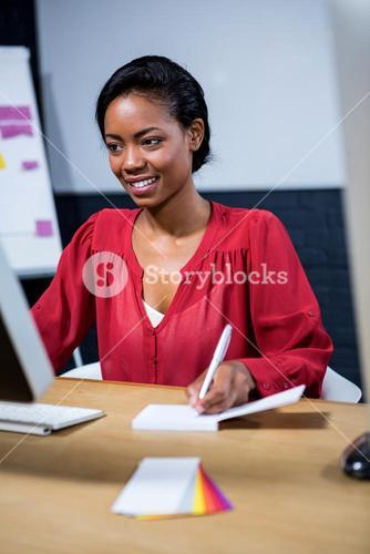 Woman noting on diary while using computer