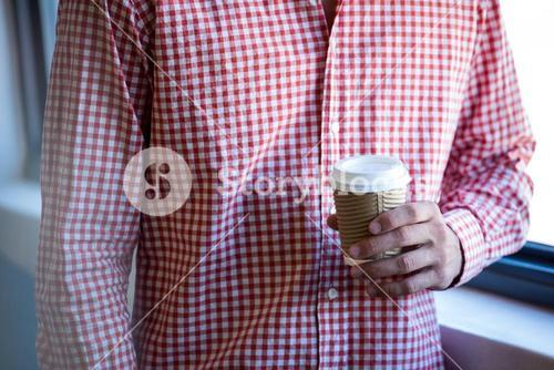 Mid section man holding disposable cup of coffee
