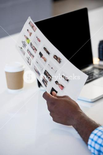 Man holding a chart with laptop on desk