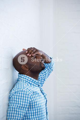 Upset man with eyes closed and hand on the forehead leaning against a wall