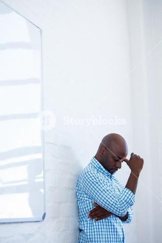 Upset man with eyes closed and finger on the forehead leaning against a wall