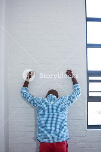 Upset man leaning against wall