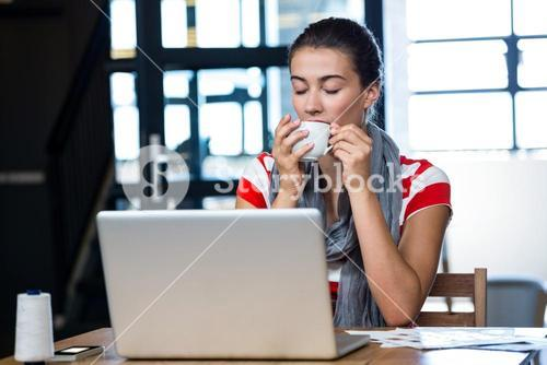 Woman having coffee at desk